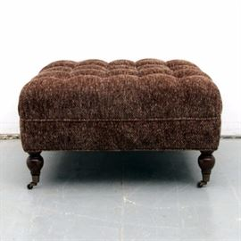 Tufted Ottoman on Casters: A tufted ottoman on casters. This square piece features tufted brown woven upholstery. It stands on four turned wooden legs ending in casters. There are no visible maker's marks.