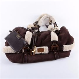 Dolce & Gabbana Shearling Tote: A Dolce & Gabbana shearling tote. This brown suede tote bag features brown leather and fur trim, a gold tone logo plaque to the center, and adjustable fur and brown leather straps with gold tone hardware. The interior is lined with the clipped wool of the shearling, and includes a brown pebbled leather zipper pouch marked with a gold tone logo plaque.