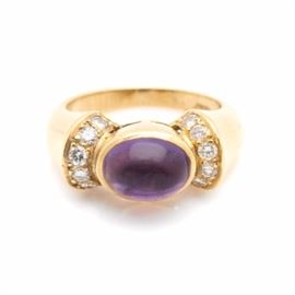 18K Yellow Gold Amethyst and Diamond Ring: A 18K yellow gold amethyst and diamond ring. This ring showcases an amethyst center, accented by twelve diamonds adorned atop the flared and ridged shoulders. The total carat weight of all diamonds included is 0.36 ctw.