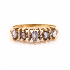 14K Yellow Gold Tanzanite and Diamond Ring: A 14K yellow gold tanzanite and diamond ring. This ring features alternating marquise cut tanzanite stones and baguette diamonds in an open stepped gallery.