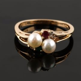 14K Yellow Gold Cultured Pearl, Emerald, Ruby and Diamond Ring: A 14K yellow gold cultured pearl, emerald, ruby and diamond ring. This ring features two cultured pearls set on a diagonal, with a diamond and emerald accent on one side, and a diamond and ruby accent on the other side.