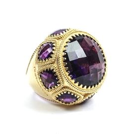 Rebecca Designer Gold Tone Ring with Purple Amethysts: A gold tone costume ring with checkerboard-cut purple amethyst gemstones, by Rebecca. The ring has a very wide shank and features a round center stone, surrounded by smaller stones, all in sawtooth bezel settings.