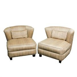 Pair of Custom Upholstered Lounge Chairs: A pair of custom upholstered, arm-less lounge chairs, each having a curved back with lumbar pillow and a tight seat and welted apron, covered on a beige, textured strie fabric. The chairs sit on four wooden feet.