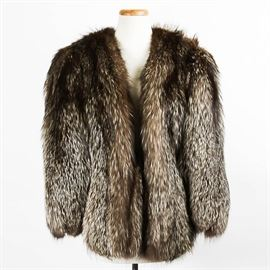 "Vintage Fox Fur Shawl: A vintage collarless fox fur shawl labeled ""Furs By Berkower Detroit"". The shawl is made of a very soft gray tipped brown fur. It has a shawl collar and long, open sleeves, with a scalloped hem. It is lined in black satin. The arms can be unsnapped to hang free."