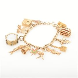 10K and 14K Yellow Gold Charm Bracelet: A 10K and 14K yellow gold charm bracelet. The bracelet, leaf and Capital charm is comprised of 10K yellow gold, and all of the other charms are 14K yellow gold. The OSU pendant and drum is gold filled base metal.