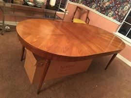 "Kindel Oval Table- Top is four pieced matched veneer fruitwood Top closed: 42 x 52. Top open: 42 x 100 (3-16"" leaves with apron with original storage box underneath)"