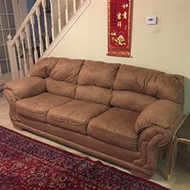 Sofa made of soft tan material. Clean and comfortable There are two of these