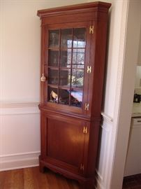 One of two mahogany corner cabinets with glass door and shelves
