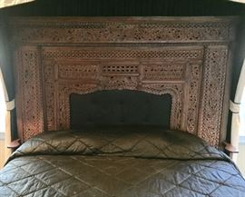 Antique hand-carved wood fireplace surround that has been converted into a king size headboard