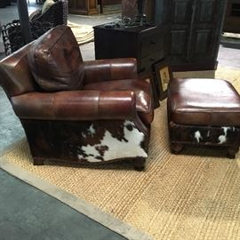 Handcock and Moore leather arm chair and ottoman, featuring cow hide details.