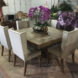 Rustic dining table with beige dining chairs, on a muted rug having an all over floral field