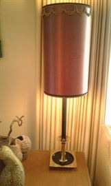 Lovely paired 1960's lamp with brass base and original lamp shade which are staged on paired Mid-Century lamp tables.