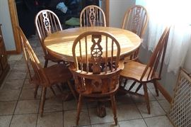 Round oak claw foot table and six oak chairs.