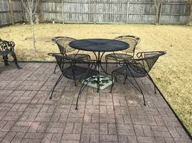 Wrought iron table and 4 chairs, also there is a very nice umbrella and stand.