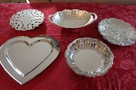 Lot#4 5 Silver-plate Dishes, platters & trivet. Lot includes: 1 silver plate round trivet; Heart Shaped platter; Round silver plate bowl; Ikora Oval Silver plate bowl with handles; Oval leaf patterned silver plate platter by Oneida
