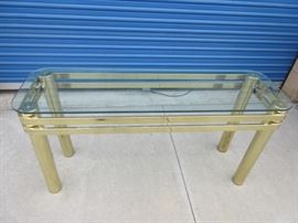 Glass top with gold tone brass-like legs sofa table