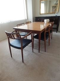 Mid Century Modern dining room table/ 6 chairs. Sideboard to the back has a silver drawer by Haverty. Also, a lovely beveled mirror.