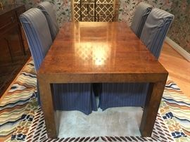 Beautiful burled wood dining table. Simple design, elegant detail! There are two leaves that can be added to increase length of the table.  Four parsons chairs with slip covers. See additional pictures with covers removed.