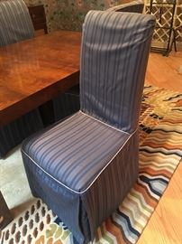 One of four parsons chairs with stripped blue slip covers.