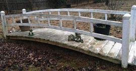 Long, quaint, garden bridge and frog yard art.