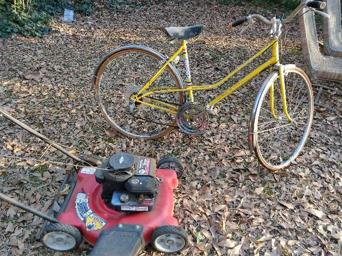 """Super Duper vintage 10-speed women's bike """"Belle De Paris"""",  in Mellow Yellow, part of their Tour de France collection, by Astra.                                                                   Astride this man-magnet bike is a lovely Briggs & Stratton 300 series side discharge push mower.               It's soon to be Speedo season, so get those glutes in shape by pushing this baby around your white picket fence!"""
