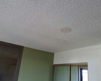 "The inside of neighbor at 2483 master bedroom.  4 stains.  Long line to left of circle indicates one of many ""gashes"" in his roof.  Master bedroom and master closet has viable water stains from leaks.  Much od which he tried to cover up with paint."