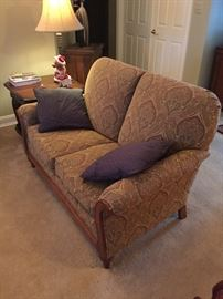 Upholstered love seat with pillows, very masculine upholstery with walnut wood