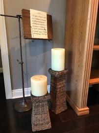 Antique music stand and rattan candle holders with candles.