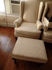 One of a pair of white wing chairs with ottomans