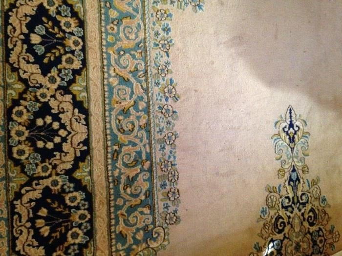 Large rug in tan, gold, and blue