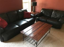 Leather couch and love seat set. Wood and metal coffee and end tables.