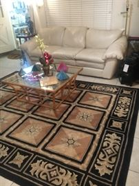 Leather sofa, great little glass & gold coffee table, tchotchkes, thick rug and more!
