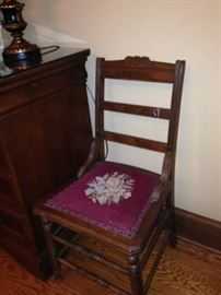 One of two matching needlepoint seat antique chairs