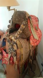 Asian horse saddle propped on wooden stand, with red/yellow textile and silver ornaments gifted from the Prince of Nepal circa 1960s.