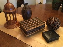 Accessories to love...wooden architectural model with steps, columns, and dome, 6 inch round twig ball, wooden box with hinged top, black and gold diamond pattern, black leather box with embossed design on top, bulbous shaped brown finish pottery vase, impressed flowers and etched lines at base