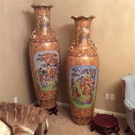 Exquisite Asian floor vases show figural painted scenes. Six feet in height, each has a fluted opening and comes with its own curved lacquer encrusted riser.
