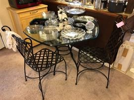 Very nice glass top table with wrought iron base and to wrought iron chairs