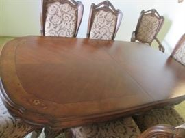 Sculpted Oval Shape of the Dining Room Table Top with Inlay Details at the 4 corners