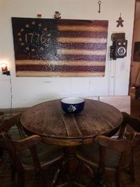 Oak table with pedestal that has claw feet on the bottom with two chairs