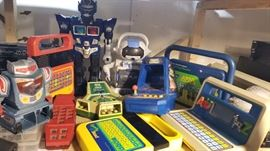 Vintage electronic hand held games and toy plastic robots with Speak 'N Spells and mini arcade Space Invaders