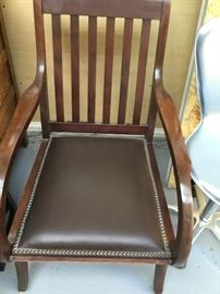 Antique brown leather side arm chair with nail heads and rollers.