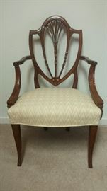 Circa 1780-1800 Hepplewhite Mahogany Shield Back Armchair; shield shaped mouled back consisting of 3 bow knot carved slats withg floral carved centers, the cenral slat with carved bellflowers -- continuing to 5 moulded radiates; mouled serpentine shaped armrests with rosette carved terminals supported by moulded invurning arm supports; overupholstered bowed seat; mouled squared & tapered front legs with flaring fee.  New York.  We guarantee this armchair to be absolutely & unmistakably genuine as represented in the above description. Purchased November 1, 1977