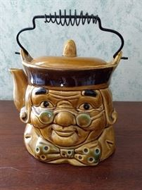 This novelty teapot features a likeness of Ben Franklin, with signature round spectacles and bowtie. Hold by the top handle and tip to the side to pour from the spout where Ben's ear would be. The pot is a glazed honey gold porcelain with black and green accents and has a metal top handle and fitted cover. Japan stamped on bottom. $30