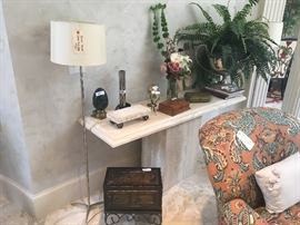 Palmer Hargrave lamps ($320/each-2 available); Travertine console table ($795); wooden box on stand ($48); assorted home decor items; silk plant; floral arrangement