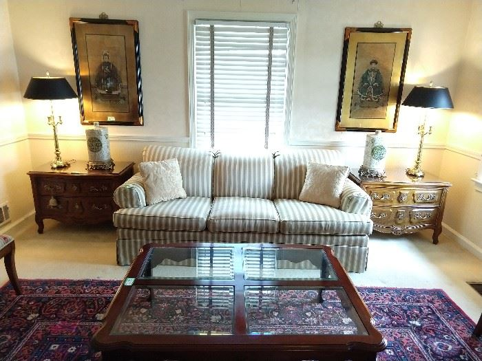 "One of a pair of Ethan Allen upholstered sofas, flanked by a pair of vintage Henredon Villandry French Louis-XV-Style walnut chests; they measure 34"" wide x 19 1/2"" deep x 24 1/2"" tall. There is an  Ethan Allen mahogany coffee table, with beveled glass inserts and a 3-drawer mahogany sofa table. Above the Henredon chests, are a pair of Chinese ancestral paintings, on cork, also a pair of 3-way vintage Stiffel lamps and pair of Asian porcelain vases, on brass bases."
