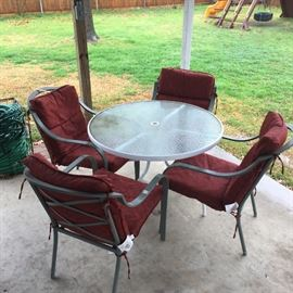 Patio set round glass top table with four chairs and umbrella stand