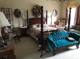 A bedroom showing an incredible carved poster bed, Victorian settee, and other quality furniture and decorative objects