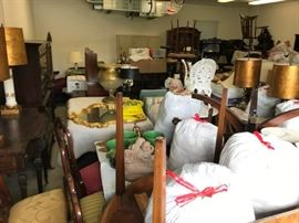 Beautiful furniture, decorative items, and bags of linens waiting for the May sale....