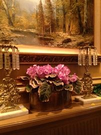 Antique lusters and floral arrangement; framed scenic view