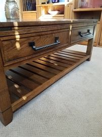 Solid wood coffee table with drawer and shelf for storage. It has a matching end table